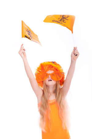 young blond girl with orange wig and hat waving orange flags in studio against white background