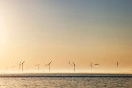 lot of wind turbines at sunrise in the dutch province of Flevoland photo