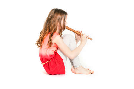 young girl sitting with soprano recorder and white background Stock Photo