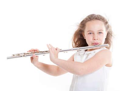 flauta: niña tocando la flauta contra el fondo blanco en el estudio Foto de archivo