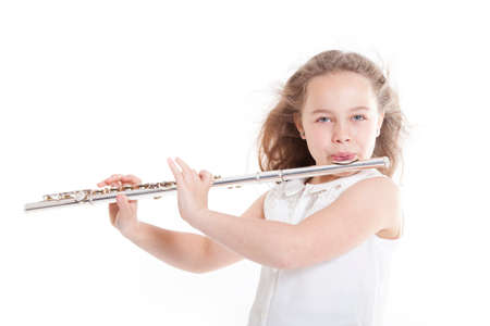 flute key: young girl playing the flute against white background in studio