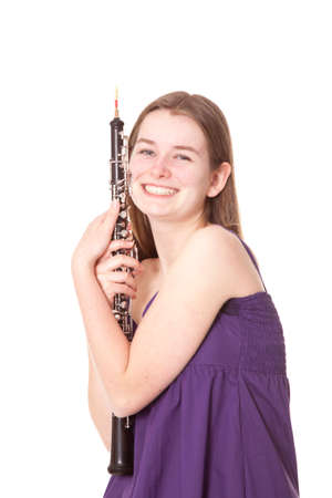 smiling girl in purple dress with oboe against white background photo