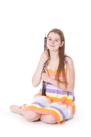 oboe: sitting girl in colorful dress with oboe against white background Stock Photo
