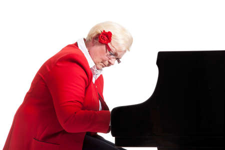 elderly lady in red playing the grand piano in studio with white background Stock Photo