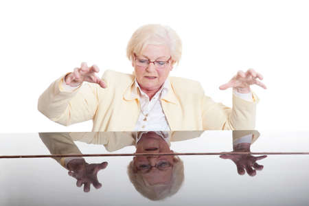 yeloow: elderly lady in yeloow playing the grand piano in studio with white background