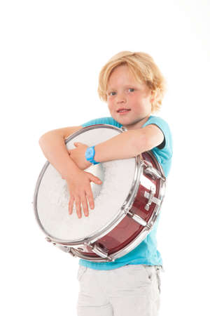 young blond boy holding drum against white background