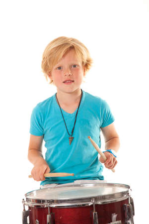 young boy drumming against white background photo