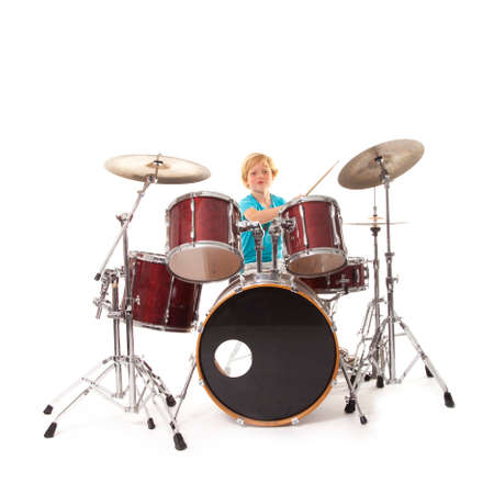 playing instrument: young boy playing drums against white background Stock Photo