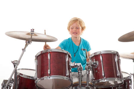 young boy playing drums against white background Stock Photo