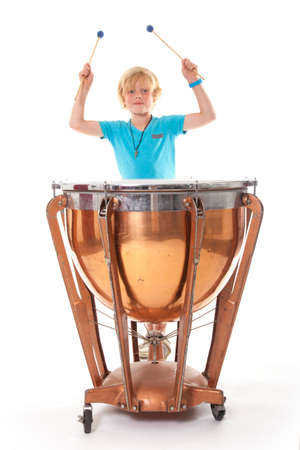 young blond boy playing kettledrum against white background