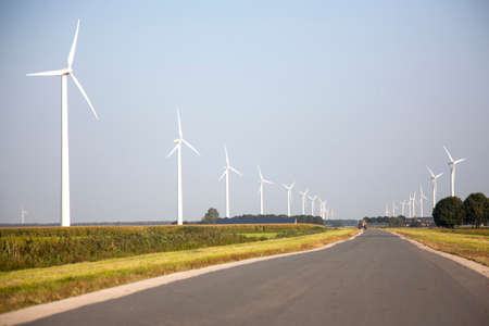road with tractor and wind turbines in the dutch province of Flevoland photo