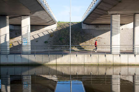 man jogs under fly-over near De Meern in The Netherlands along canal photo