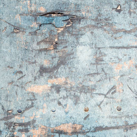 abstract background consisting of weathered board with old blue paint and bolts photo