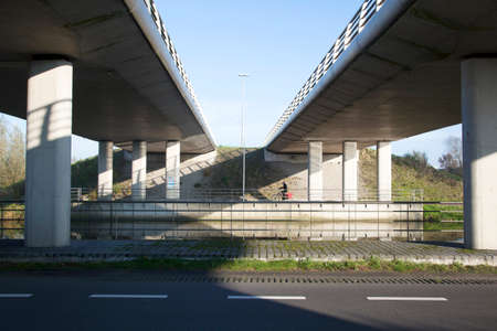 man on bicycle near De Meern under fly-over in The Netherlands photo