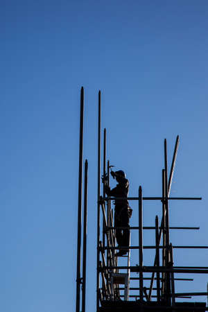 silhouette of construction worker with hammer on scaffolding photo