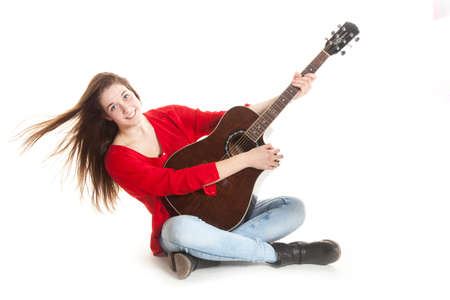 teenage girl sits and holds guitar in studio with white background photo