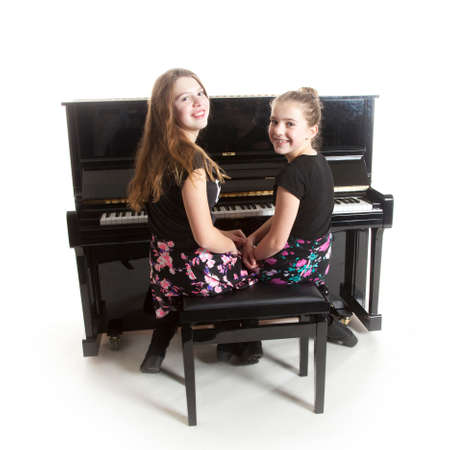 two teenage girls and black upright piano in studio against white background Standard-Bild