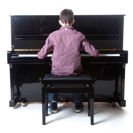 teenage boy sits at upright piano in studio with white background