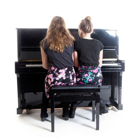 upright piano: two teenage girls and black upright piano in studio against white background Stock Photo