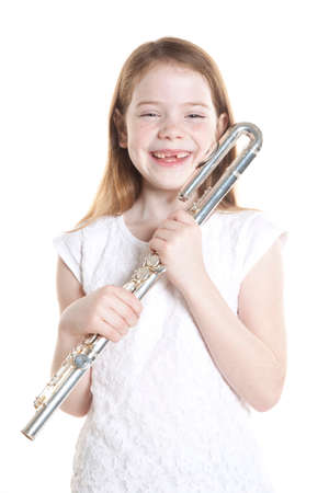 young girl with red hair and missing teeth holding flute in studio against white background Stock Photo