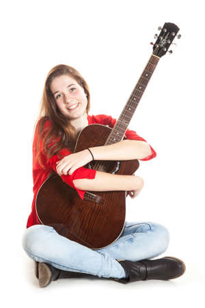 teenage girl sits and embraces guitar in studio with white background