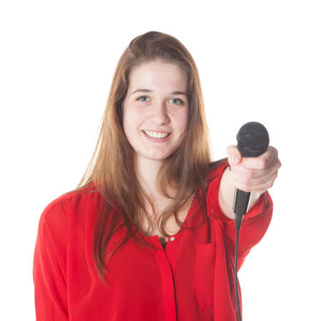 young brunette with microphone in studio against white background Stock Photo
