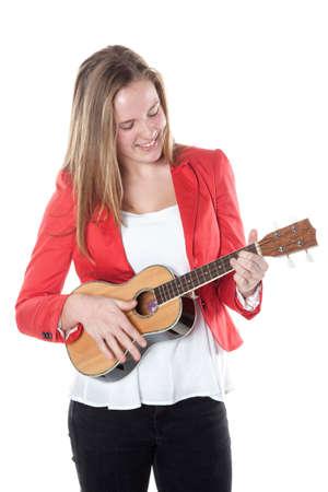 teenage girl plays ukulele in studio against white background