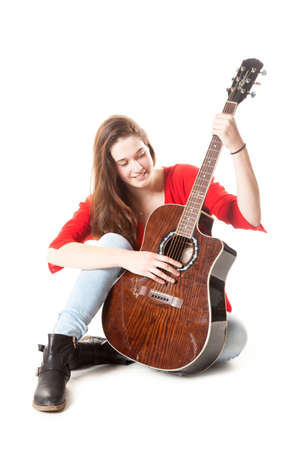 teenage girl sits and holds guitar in studio with white background Stock Photo
