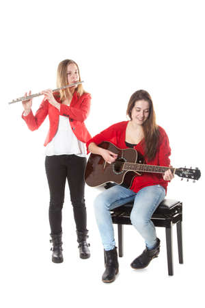 two teenage sisters play flute and guitar in studio with white background