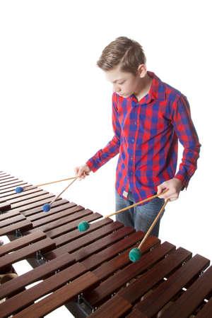 10 代の少年が白い背景に、スタジオでマリンバを演奏