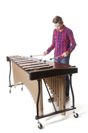 teenage boy playing the marimba in studio against white background