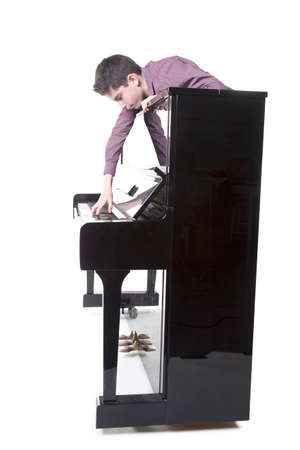 teenage boy and upright black piano in studio with white background Stock Photo