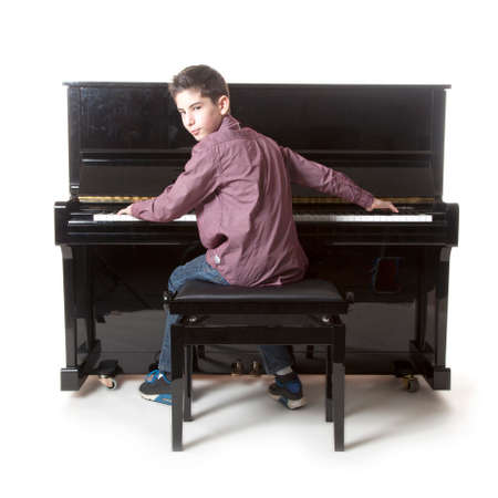 teenage boy plays the piano in studio with white background