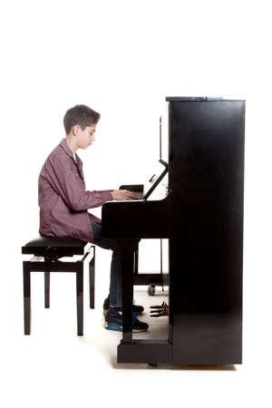 pianista: adolescente toca el piano en el estudio con fondo blanco