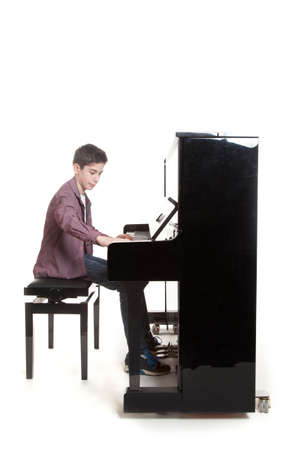 keyboard instrument: teenage boy plays the piano in studio with white background