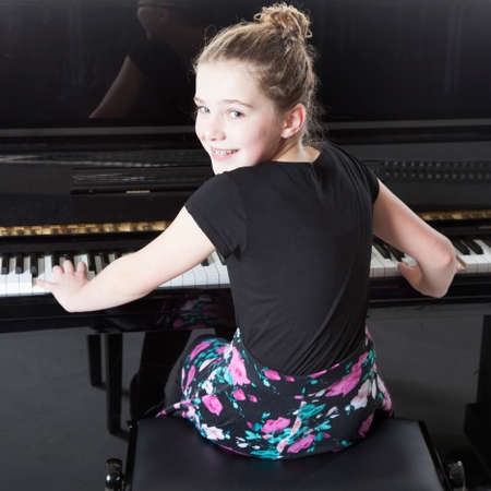 upright piano: teenage girl plays the piano in studio with white background