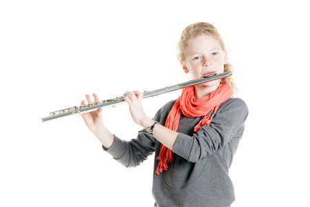 silver flute: young girl with red hair and freckles plays flute in studio against white background