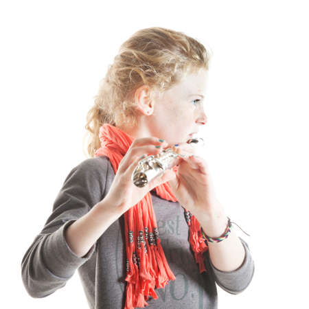 young girl with red hair and freckles plays flute in studio against white background