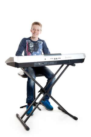 teenage boy sitting at keyboard playing music
