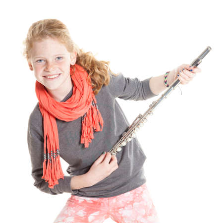 silver flute: young girl with red hair and freckles holding flute in studio against white background