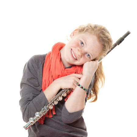 young girl with red hair and freckles with flute in studio against white background photo