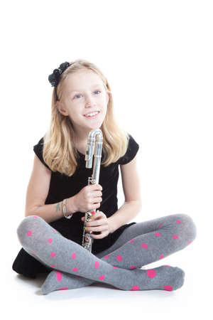 young blond smiling girl holding flute in studio against white background