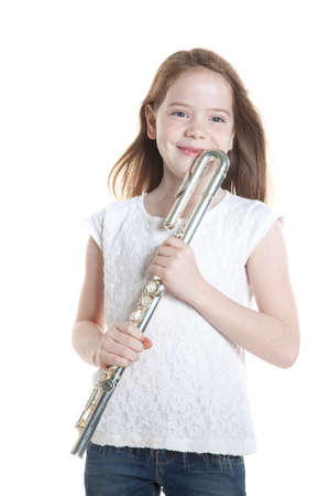 young girl with brown hair holds flute in studio against white background