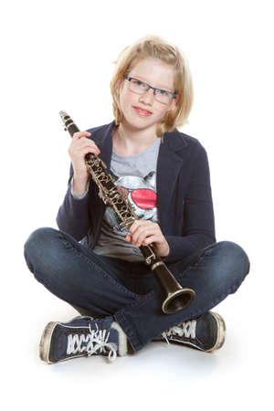 jong blond meisje zit met klarinet in de studio tegen een witte achtergrond Stockfoto