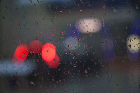 red lights of traffic seen through wet windshield during rainfall