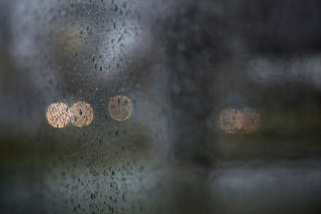 lonliness: car lights of traffic seen through wet windshield during rainfall Stock Photo