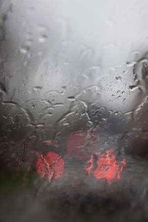 lonliness: red lights of traffic seen through wet windshield during rainfall