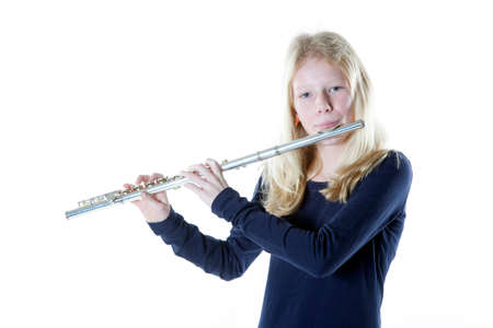 silver flute: young blond girl playing flute in studio against white background