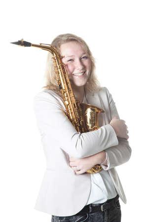 caucasian teenage girl hugs saxophone against white background in studio Stock Photo