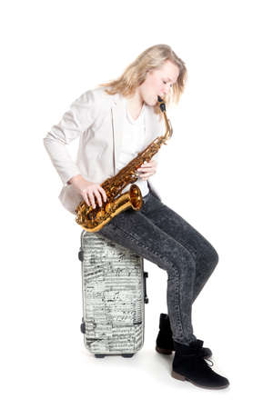teenage girl with saxophone on suitcase with musical notes against white background in studio Stock Photo
